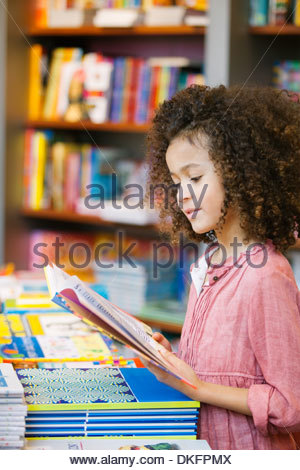 Young girl reading storybook in library - Stock Photo