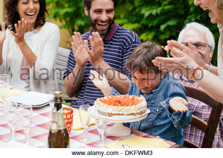 Boy being surprised with birthday cake - Stock Photo