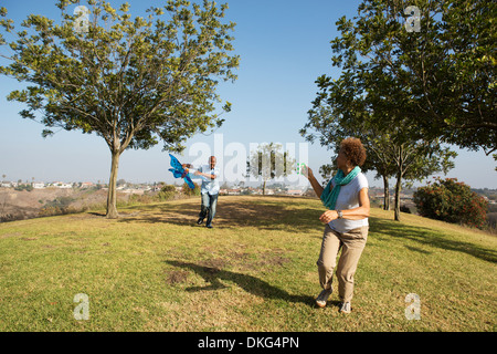 Senior couple running in park with kite - Stock Photo
