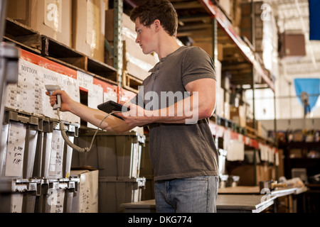 Worker in warehouse scanning barcode on cardboard box - Stock Photo