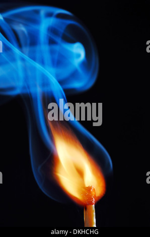 lighting a match on black background - Stock Photo