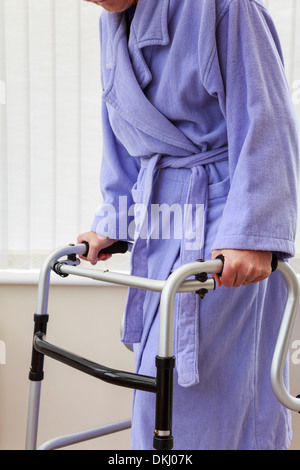 Elderly senior woman wearing a purple bathrobe holding using a zimmer frame walker or support trolley for walking - Stock Photo