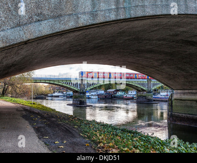 Low tide view of the steel Richmond railway bridge through  concrete arch of the Twickenham road bridge - River - Stock Photo
