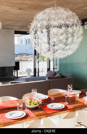 Chandelier over set dining table in modern dining room - Stock Photo