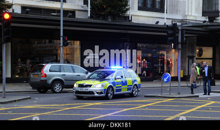 London Metropolitan Police car with blue lights flashing on emergency call out in Kensington High Street London - Stock Photo
