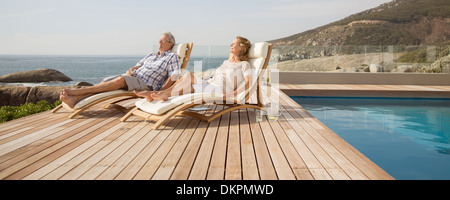 Older couple relaxing in lawn chairs by pool - Stock Photo