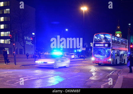 Met police car with blue lights illuminating night sky on Westminster Bridge with London bus waiting at red traffic - Stock Photo