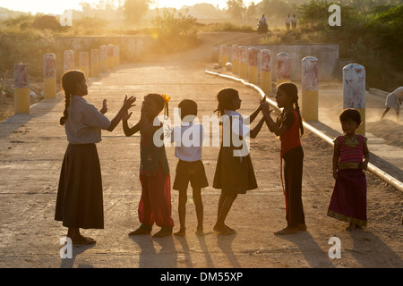 Indian girls playing on a bridge in sunlight outside their rural Indian village with lens flare. Andhra Pradesh, - Stock Photo