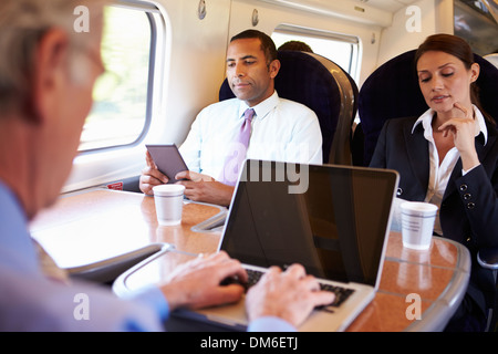 Businessman Commuting To Work On Train And Using Laptop - Stock Photo