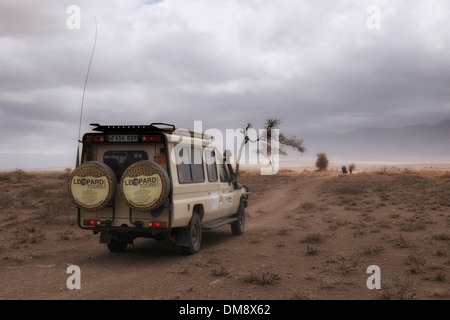 A Safari Jeep driving through the plains of the Ngorongoro Conservation Area in the Crater Highlands area of Tanzania - Stock Photo