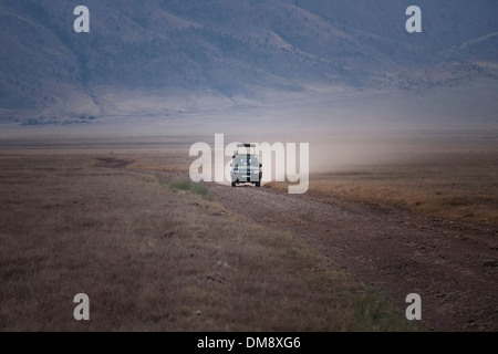 An open topped Safari Jeep driving through the plains of the Ngorongoro Conservation Area in the Crater Highlands - Stock Photo