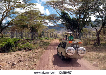 Tourists in open topped Safari Jeep driving through the Ngorongoro Conservation Area and a World Heritage Site in - Stock Photo