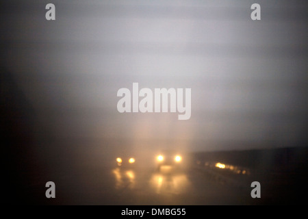 Cars traveling on a misty highway. - Stock Photo