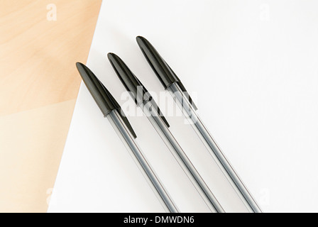 Three ball point pens lined up in a row on a white background. - Stock Photo