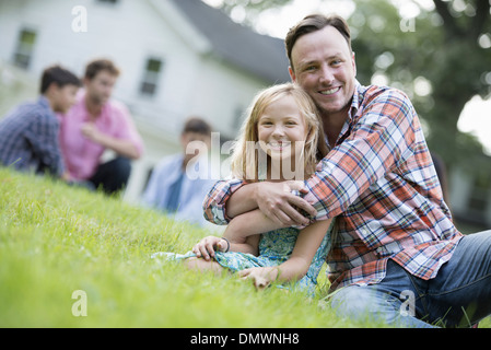 A father and daughter at a summer party sitting on  grass. - Stock Photo