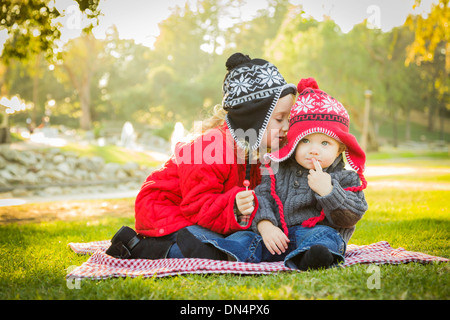 Little Girl Whispers A Secret to Her Baby Brother Wearing Winter Coats and Hats Sitting Outdoors at the Park. - Stock Photo