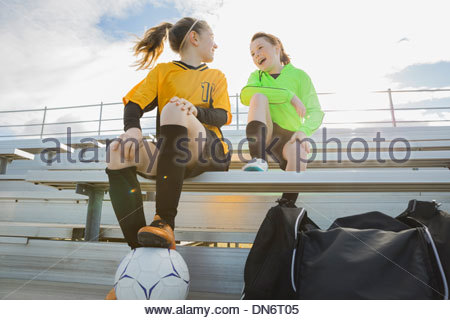 Girls in soccer uniforms sitting on bleachers - Stock Photo