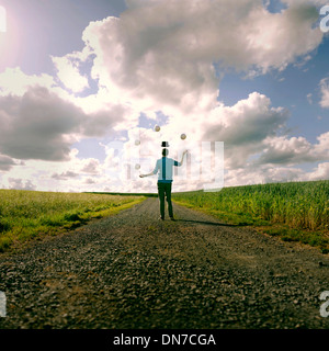 Young man with floating hat juggling in the field - Stock Photo