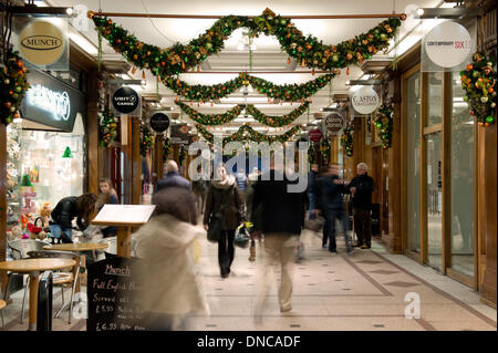 Manchester, UK. 22nd December, 2013. Christmas shoppers walk past independent stores in a small shopping mall during - Stock Photo