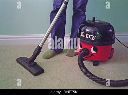 Caucasian Man Vacuuming a Carpet with a Henry Vacuum Cleaner MODEL RELEASED - Stock Photo