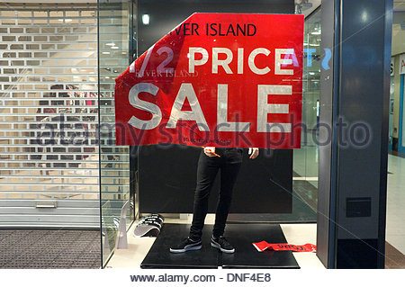 Gloucester, UK. 24th December 2013. A shop worker puts up a '1/2 PRICE SALE' poster in the display window of River - Stock Photo
