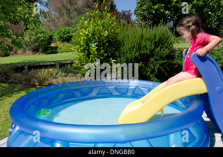 Child (girl) slides on a slide into cool waters in a children inflatable pool on a hot sunny day at home garden. - Stock Photo