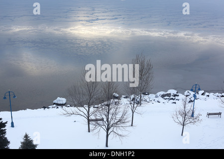 A view from above of a bench on the shore of Lake Superior in winter. - Stock Photo