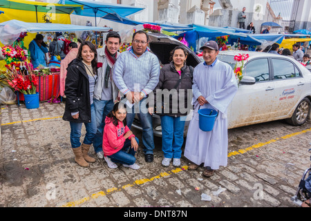 A small family grouping at the blessing of the automobiles at the Basilica of Our Lady of Copacabana in Copacabana, - Stock Photo