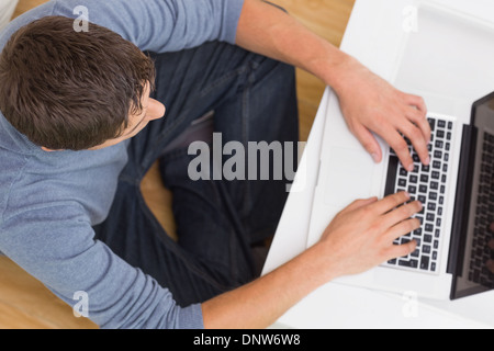 Overhead view of a man using laptop at home - Stock Photo