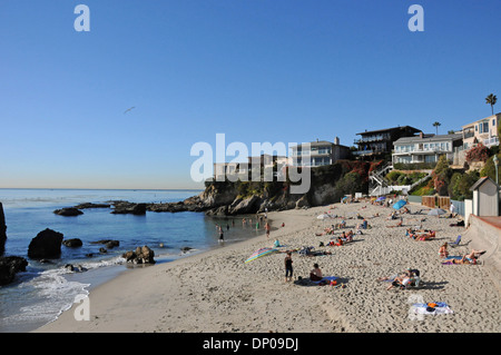 Coastal homes and sun bathers at Woods Cove in Laguna Beach on a warm winter day in  Southern California - Stock Photo