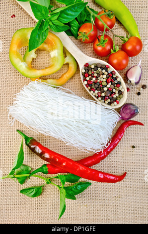 Rice noodles thin, tomatoes, different peppers, garlic, basil on a background of sack cloth - Stock Photo