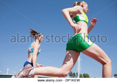 Runners jumping hurdles on track - Stock Photo