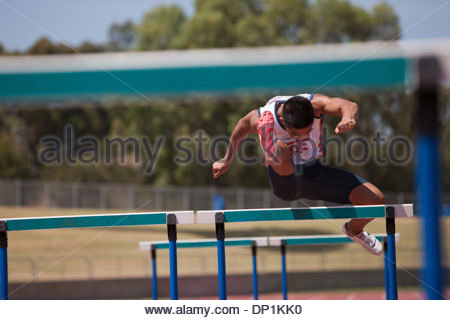 Runner jumping hurdles on track - Stock Photo