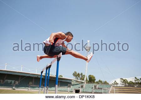 Runner jumping hurdles on track - Stock Photo