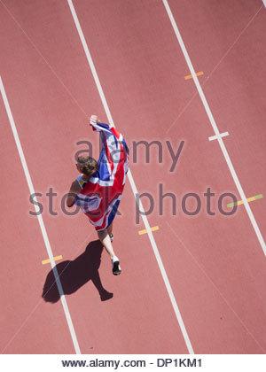 Runner celebrating with British flag on track - Stock Photo