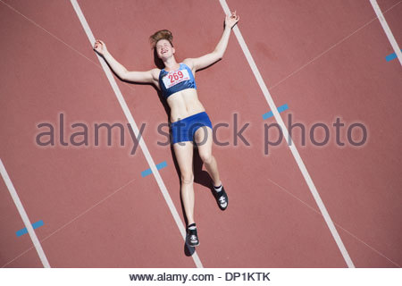 Tired runner laying on track - Stock Photo