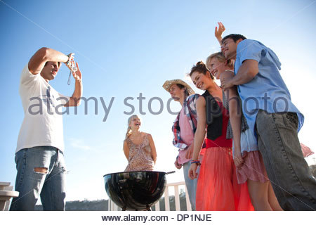 Man with digital camera taking photograph of friends - Stock Photo