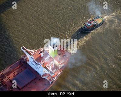 Bugsier 9 tug boat towing the Bergebulk Arctic from the harbor, Hamburg, Germany - Stock Photo