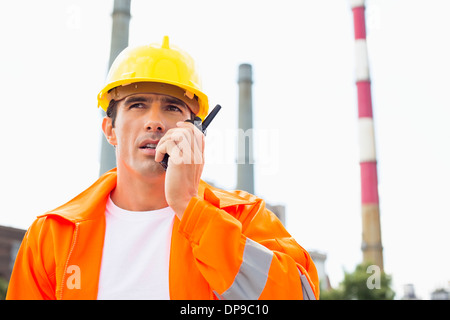 Male construction worker wearing reflective workwear communicating on walkie-talkie at site - Stock Photo