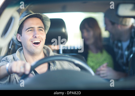 Young adult friends driving in car - Stock Photo