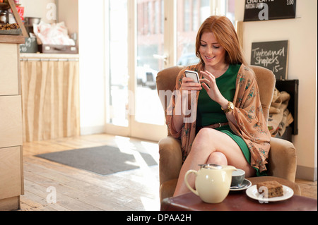 Portrait of young woman using smartphone in cafe - Stock Photo
