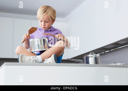 Boy sitting on kitchen counter playing drums with pans and wooden spoons - Stock Photo