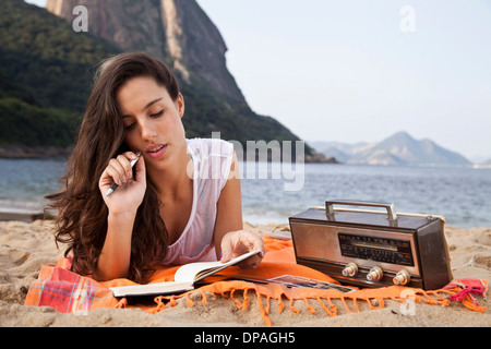 Woman on beach writing in notebook, Rio de Janeiro, Brazil - Stock Photo