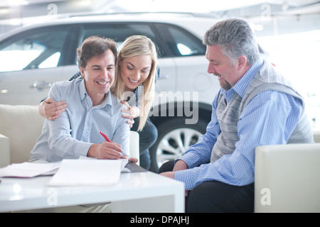 Car salesman and couple signing contract in car showroom - Stock Photo