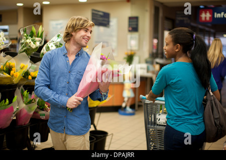 Young man selecting bunch of flowers whilst shopping - Stock Photo