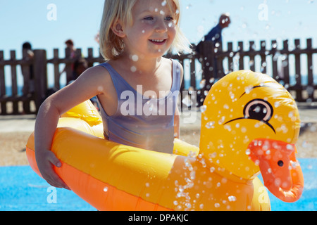 Child with duck-shaped float in pool - Stock Photo