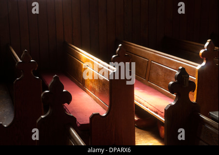 Church pews lit by window - Stock Photo