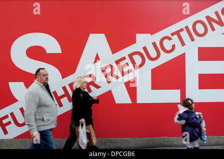 People walking past the Sale sign outside a shop - Stock Photo