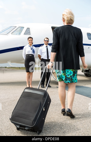 Businesswoman With Luggage Walking Towards Private Plane - Stock Photo