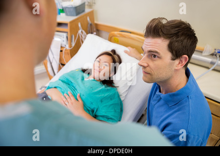Man And Pregnant Woman Listening To Nurse In Hospital - Stock Photo